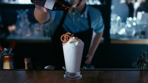 Barista adding syrup to a milk shake. 4K cinemagraph - motion photo seamless loop