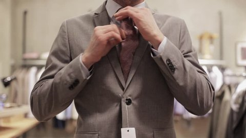 sale, shopping, fashion, style and people concept - man trying suit and taking mirror selfie by smartphone at clothing store