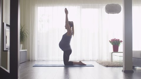Young Pregnant Woman Doing Stretching and Fitness in Living Room at Home. Shot on RED Cinema Camera.