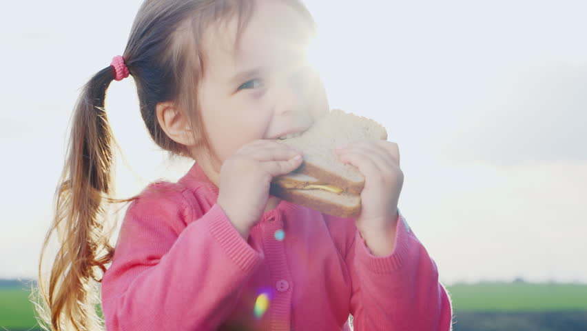 Girl three years, eating a sandwich in the sun