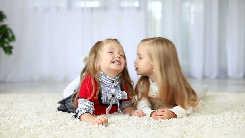 Sisters smiling while lying on the carpet. DOLLY HD