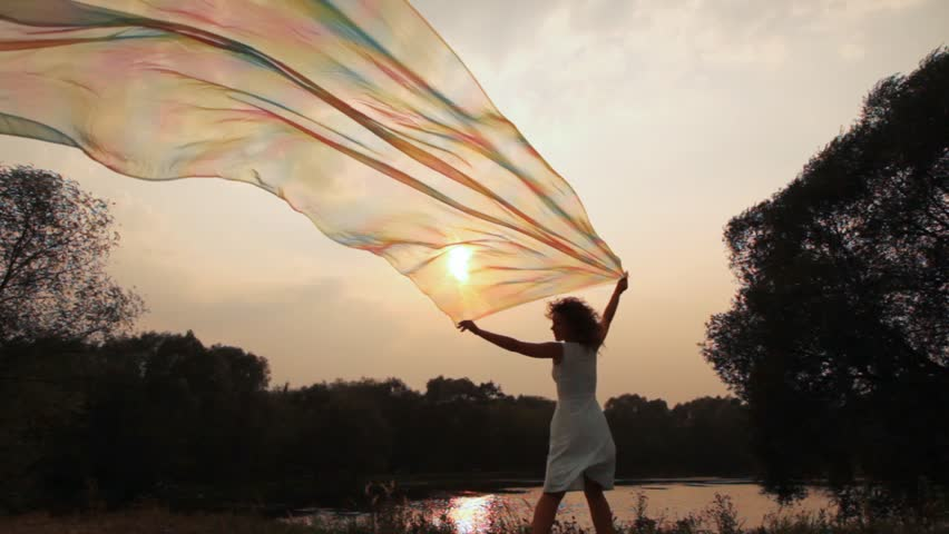woman stands on bank of lake and holds shawl which fluttering gets to camera
