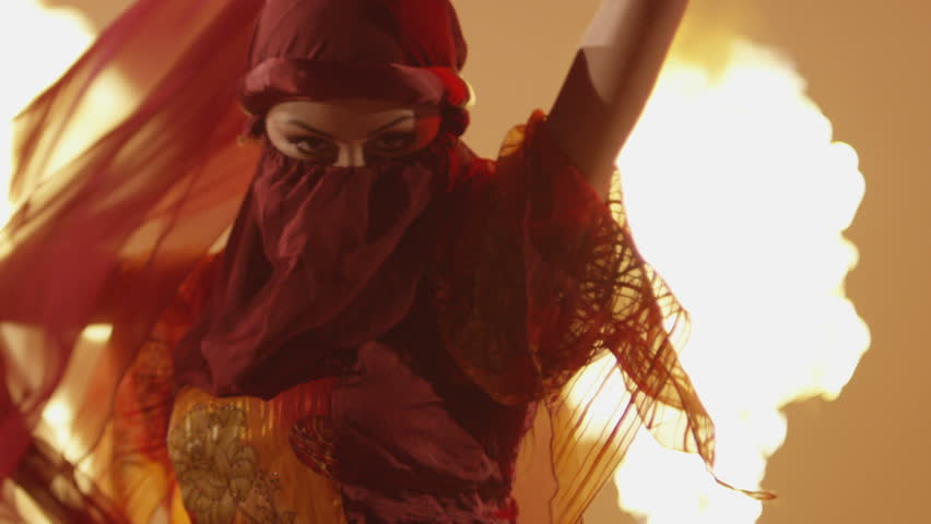 Beautiful traditional oriental belly dancer. Oriental girl dancing on red background. Studio shoot with fire.  Shot on RED EPIC DRAGON Cinema Camera in slow motion.