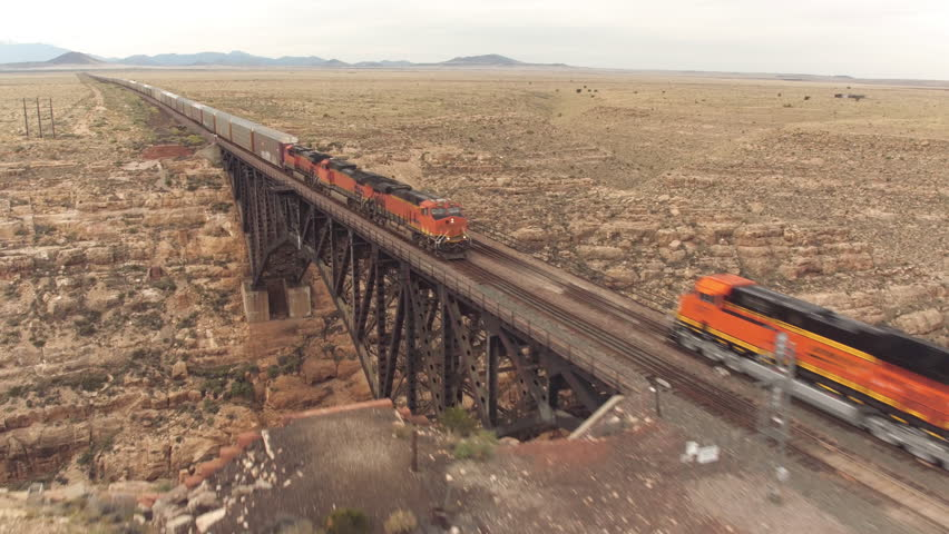 AERIAL: Two container freight trains crossing steel arch railroad bridge across the Canyon Diablo in the middle of the vast desert in Arizona. Rail freight transport delivering goods