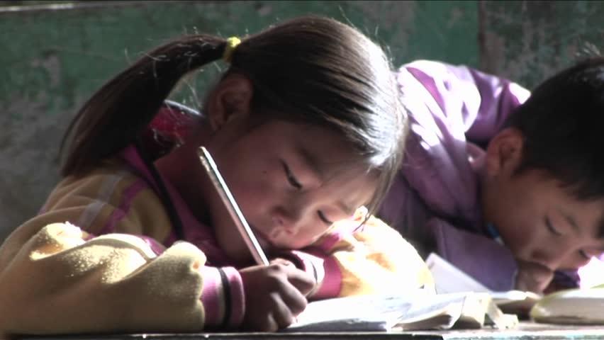 BEIJING, CHINA - CIRCA 2009: Children practice writing in a rural classroom circa 2009 in Beijing.