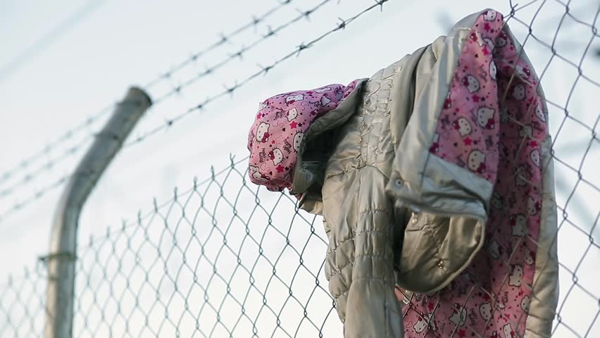 A child's jacket hangs on a razor wire fence erected to keep immigrants away.
