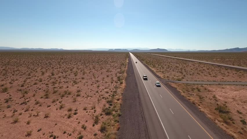 A cool aerial shot of cars and semi trucks driving on I-15 highway in the vast desert near Las Vegas Nevada | Shutterstock HD Video #15999745