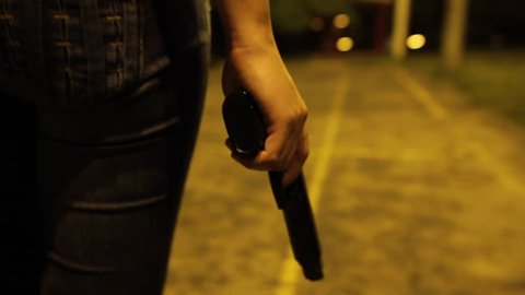 A WOMAN WALKING WITH A GUN IN HER HAND