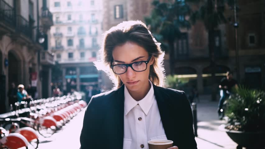 Close-up of attractive young businesswoman walking on urban street and using modern smartphone outside, sunshine, slow motion | Shutterstock HD Video #16045882