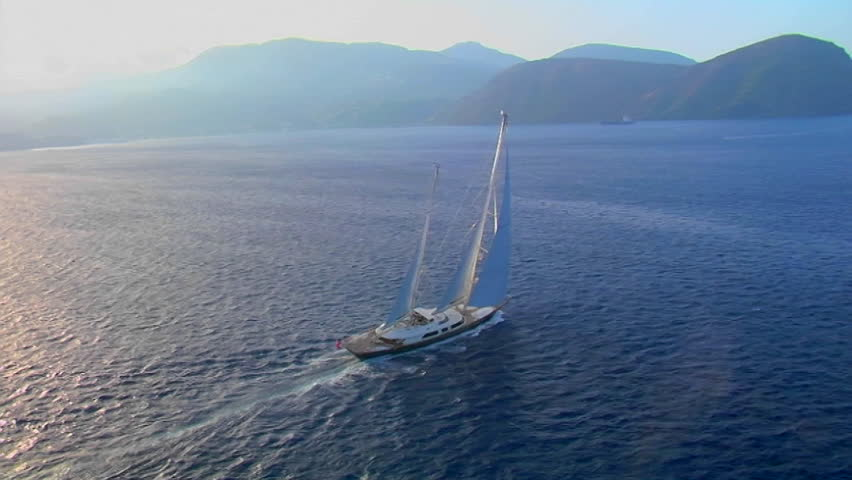 Sweeping aerial shot of large sailboat on open water during golden hour