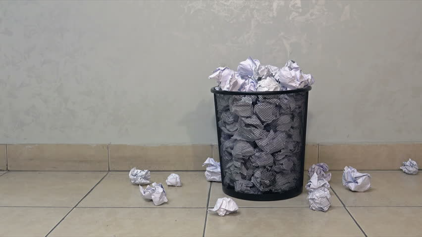 Throwing useless paper into the full waste basket in office. Papers fall on the floor