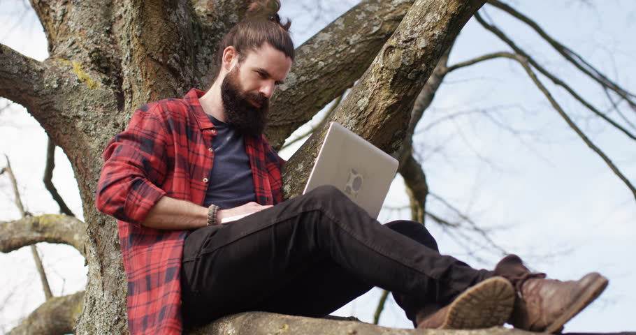 4k young man sitting on a tree trunk away from hustle and bustle of a city and working on his laptop. | Shutterstock HD Video #16143175