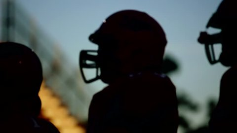 Silhouetted football players close up