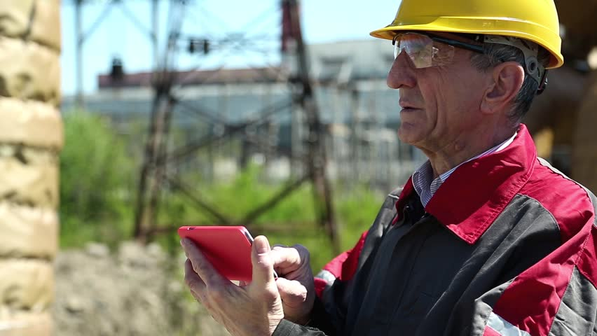 Emergency repairman with red smartphone at power station. Power engineering specialist with smartphone at heat station. Worker in yellow hard hat at heat station. Factory worker with red smartphone