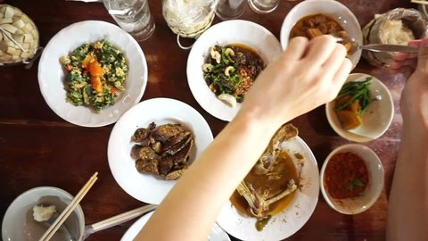 Point of view of hand eating variety traditional Thai food cuisine from top. sticky rice, curry and paste POV