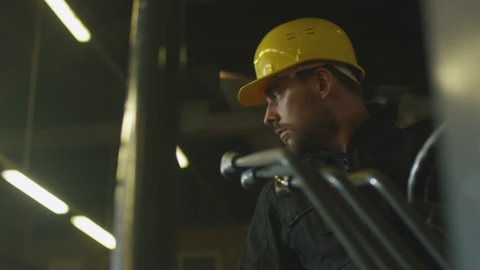 Forklift operator is driving in lumber factory warehouse. Shot on RED Cinema Camera in 4K (UHD).