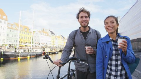 Copenhagen couple. People walking in Nyhavn, old port. Famous tourist attraction destination in Denmark Young multiracial happy couple with bicycle bike and coffee.