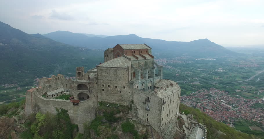 An aerial view over Val Susa, Turin, Sacra of San Michele, a medioeval building in nort of Italy, Saint Michael's Abbey, a church on the top of a mountain, alps, flying around