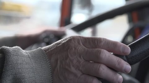 Steering wheel in use. Close up slow motion shot of hands of a senior man driving the vehicle.