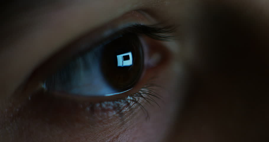the very macro eye of a very young student surfing internet web by night