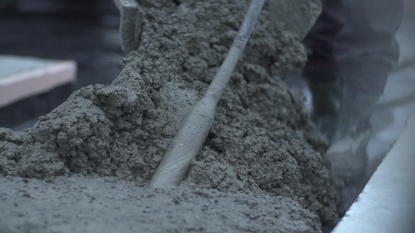 Close up and slow motion shot of  carefully mixed concrete. Manual concrete  works with a shovel at construction site.  #16248775