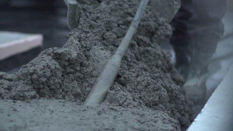 Close up and slow motion shot of  carefully mixed concrete. Manual concrete  works with a shovel at construction site.