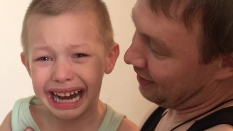 child crying, angry, and beats his father,father of the child calms