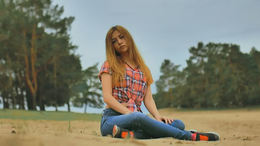 Sexy Girl In Jeans And Shirt Sitting On Sand In Forest Slow Motion ...