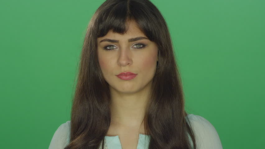 Tired beautiful brunette woman looking slightly concerned, on a green screen studio background | Shutterstock HD Video #16252675