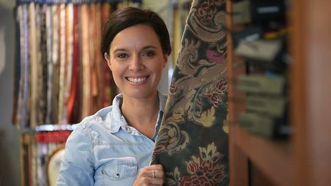 Woman in upholstery shop looking at fabric samples