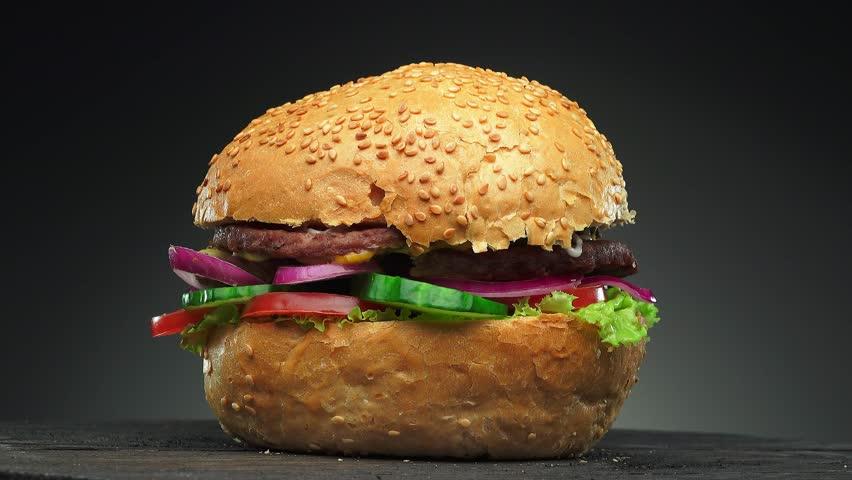 Fresh appetizing hamburger rotating on black background. Seamless loopable shot, 4k.