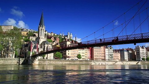 People are walking over the Passerelle Saint-Georges bridge over the Saone river in Lyon, France.