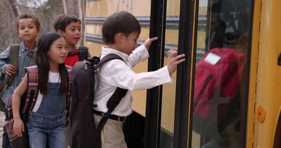 Young elementary school kids boarding a school bus
