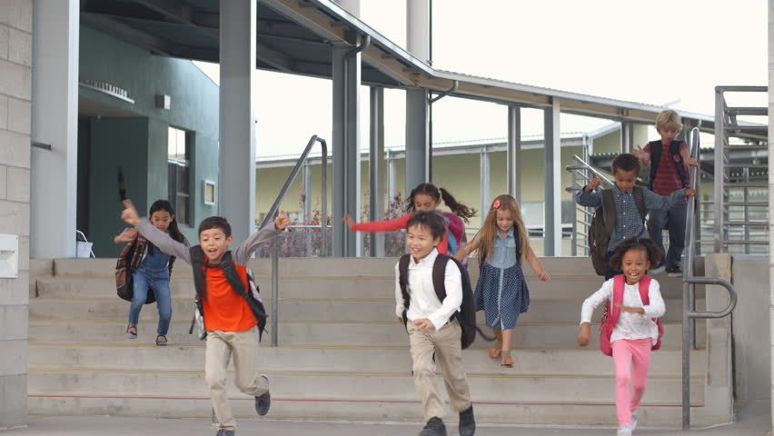 Young School Kids Jumping Down Steps As They Leave School Stock ...