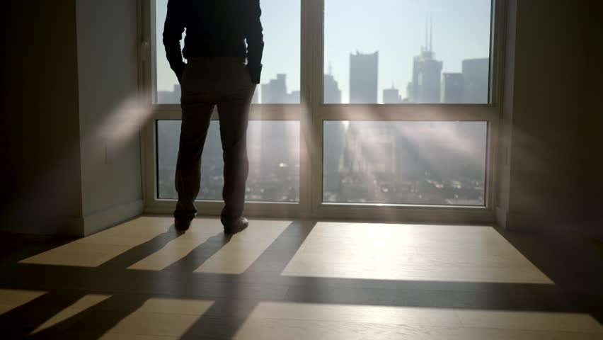 one man opening window roller blinds in the morning overlooking city panorama. sun light beams shining through window