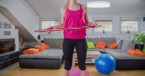 A lady is trying to exercise. She is doing a Hula-Hoop work-out. She's quite good at it. It is a great way to have fun when working out.