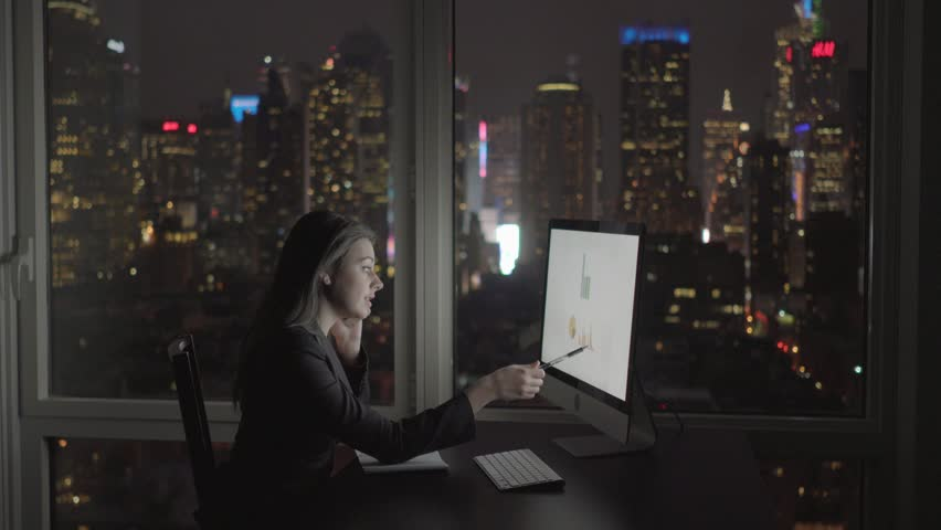 attractive caucasian women sales professional calculation earnings on computer screen. financial saleswomen working in modern office building in the city at night