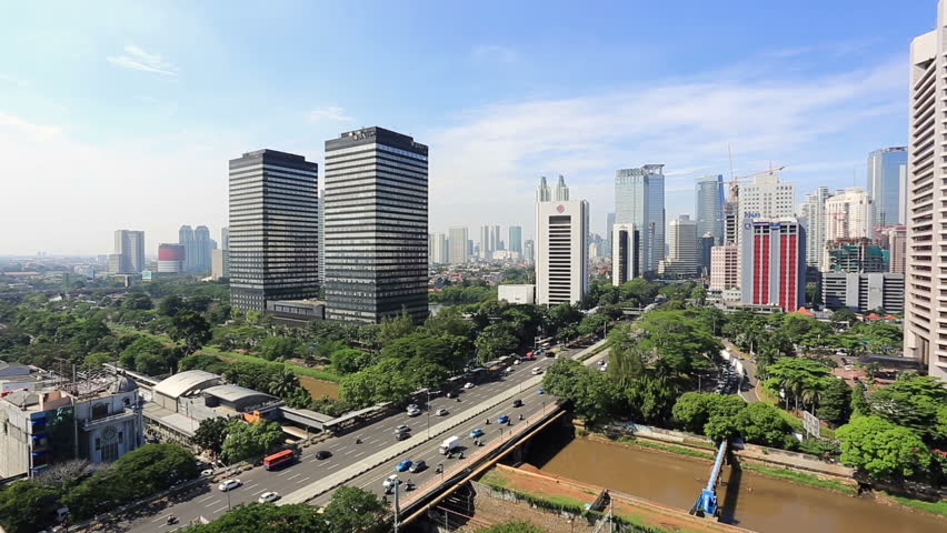 JAKARTA, INDONESIA - APRIL 17, 2016: Traffic rushes along Sudirman avenue on a bridge above the Ciliwung river in the central business district of Jakarta in Indonesia capital city.