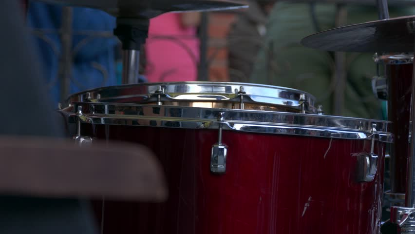 Ungraded: Drummer Playing / Drum Player / Street Musician. Drummer playing a drum set at open-air rock concert. Drum close-up. Source: Lumix DMC, ungraded H.264 from camera. (av25323u)