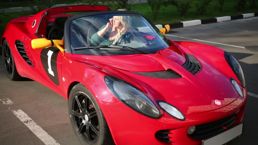 Genial Blonde Woman Sits In Red Sport Car And Talks Phone At Sunny Day   HD Stock