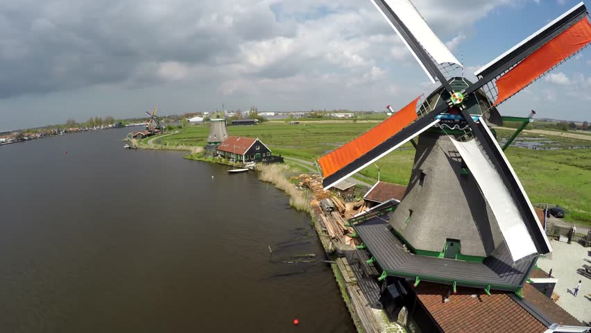 Aerial Zaanse Schans moving past windmills then turning towards mills blades turning by wind sustainable clean energy great tourist attraction Netherlands near Amsterdam drone footage bird-eye view 4k | Shutterstock HD Video #16413964