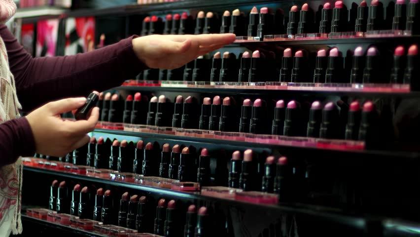 girl chooses shade of lipstick on the hand at cosmetics store