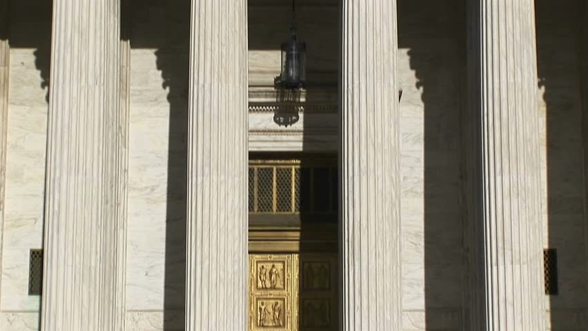 Sunlight reflects on the bright white pillars of the U.S. Supreme Court Building entrance.