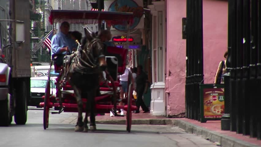 NEW ORLEANS - CIRCA 2009: A mule-drawn buggy makes its way down a crowded street in New Orleans.