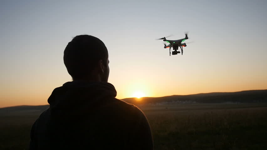 A man controls a drone at sunset | Shutterstock Video #16505374