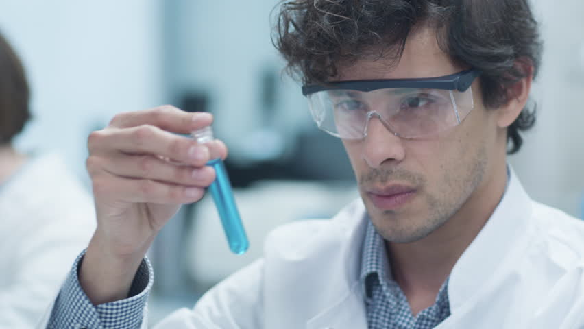 Latin Ethnicity Scientist in Safety Glasses Does Researches. Looking at Laboratory Flask. Shot on RED Cinema Camera in 4K (UHD).