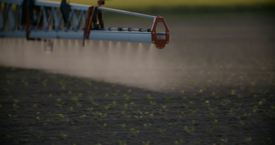 Tractor spray fertilize on field with chemicals in agriculture field.