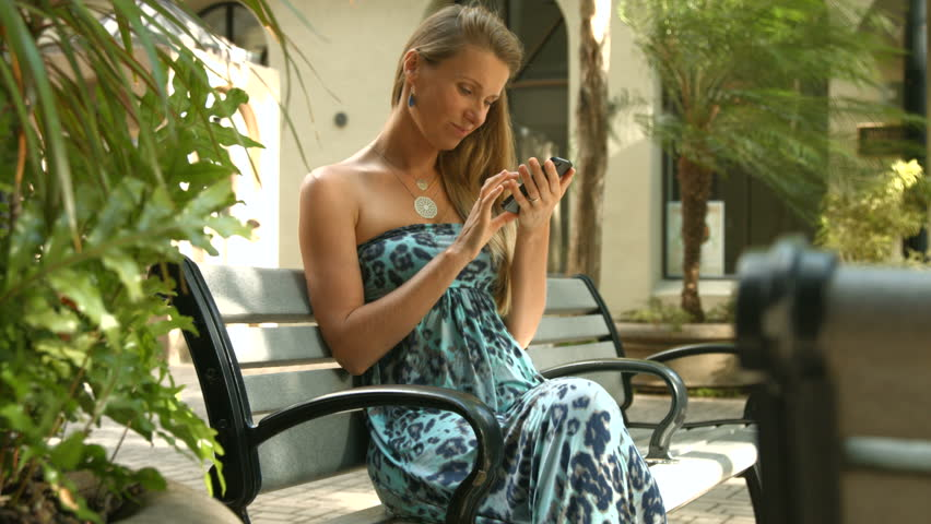4k young beautiful woman reading ebook sitting on bench in city 4k young caucasian woman texting cell phone in city pretty happy woman sitting on fandeluxe Ebook collections