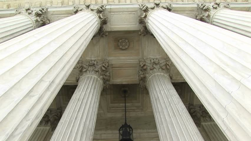 View of columns, a hanging lamp, and bronze doors at the west entrance of the Supreme Court.
