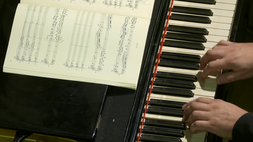 Ungraded: Pianist Playing / Piano Player / Orchestra Musician. Pianist plays piano at a classical music concert. Music sheets of VII century classics (now public-domain). (av24893u)